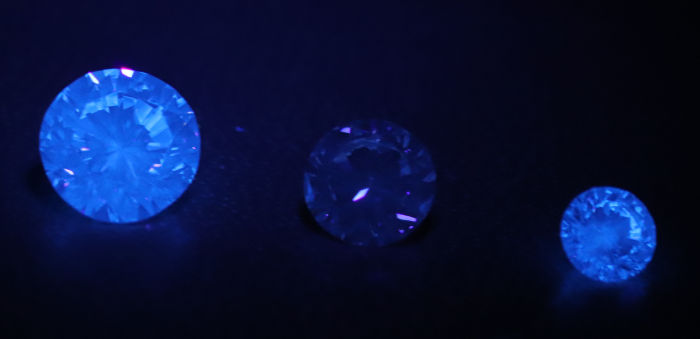 暗闇で紫外線ライトで並べったダイアモンドを照らした画像